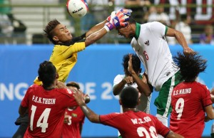 Myanmar's goalkeeper attempts to save a header from Indonesia's Pranata Hansamu Yama.