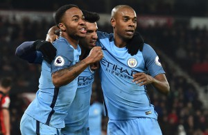 Manchester City's Argentinian striker Sergio Aguero (C) celebrates with Manchester City's English midfielder Raheem Sterling and Manchester City's Brazilian midfielder Fernandinho (R) after scoring their second goal during the English Premier League football match between Bournemouth and Manchester City at the Vitality Stadium in Bournemouth, southern England on February 13, 2017. / AFP PHOTO / Glyn KIRK / RESTRICTED TO EDITORIAL USE. No use with unauthorized audio, video, data, fixture lists, club/league logos or 'live' services. Online in-match use limited to 75 images, no video emulation. No use in betting, games or single club/league/player publications.  /